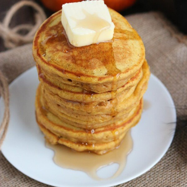 stack of pumpkin pancakes with butter and syrup and a pumpkin