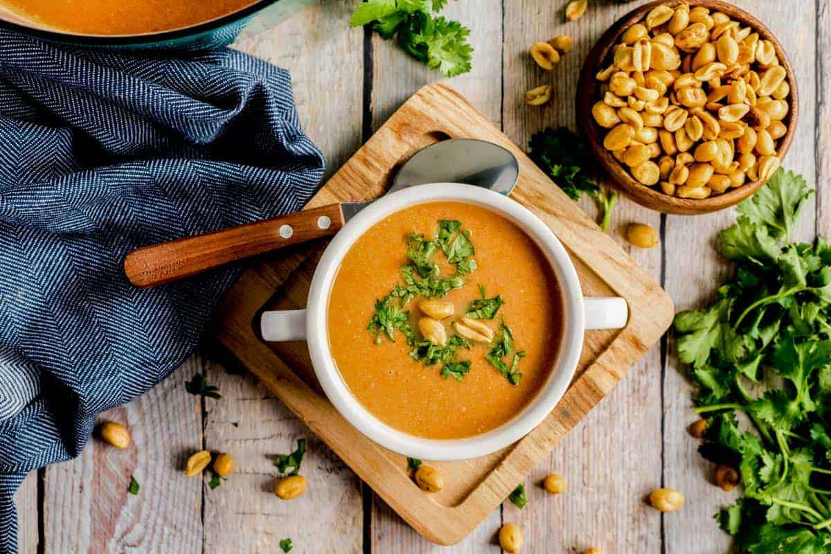 peanut soup in a white bowl on a wooden board