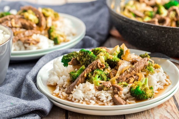 beef and broccoli on a white plate with blue napkins