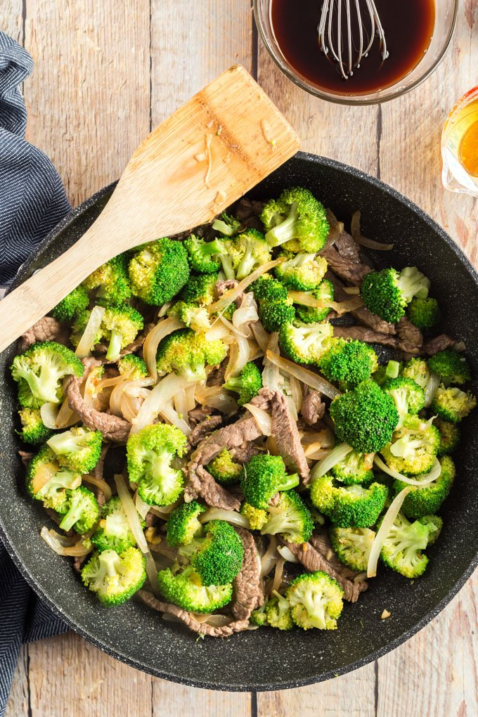 beef and broccoli in a wok with a wooden spoon
