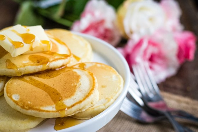 Closeup of homemade pancakes topped with butter and syrup on a white plate.