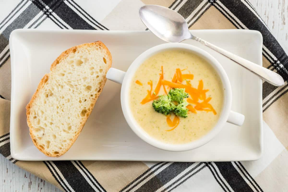 broccoli cheddar soup in a bowl, with a slice of bread and spoon
