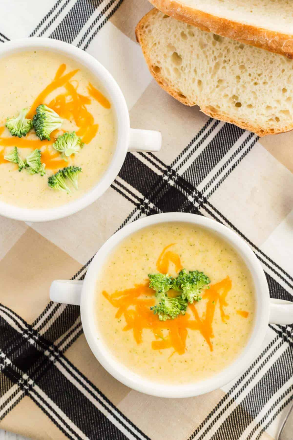 2 bowls of broccoli cheddar soup with bread