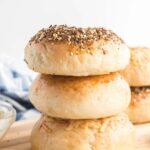 homemade bagels stacked, with a spoon and cream cheese schmear