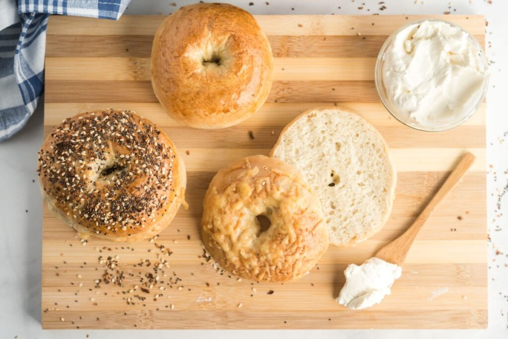 Bagels on a cutting board, cut open with  cream cheese on a knife
