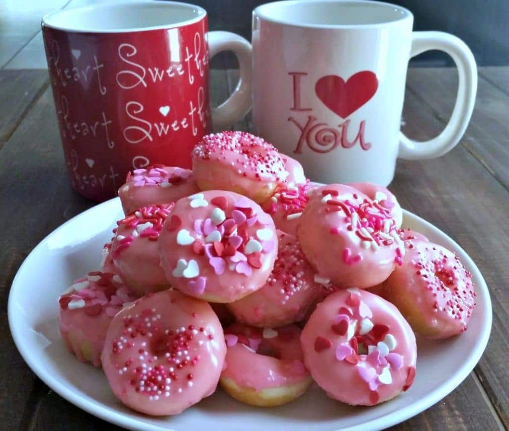 Baked donut swith pink frosting and sprinkles with 2 mugs