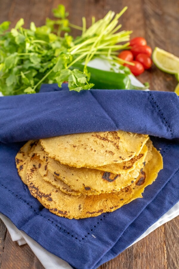 Homemade Corn Tortillas in a blue napkin with cilantro, limes and tomatoes