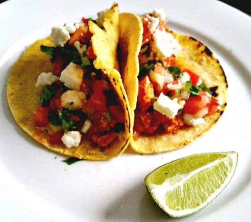 tacos made with corn tortillas on a white plate