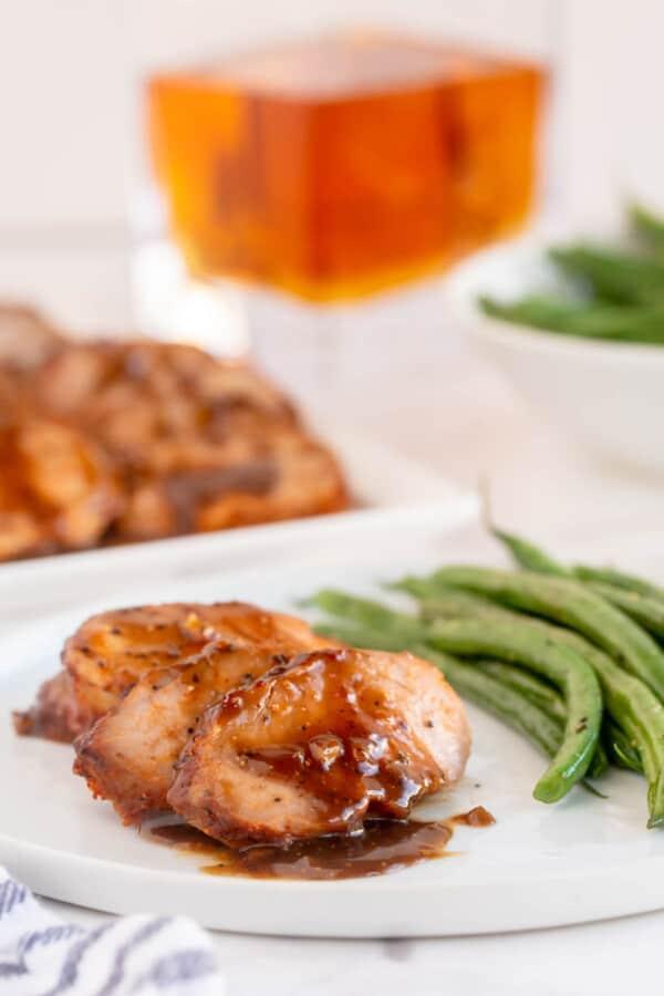 glazed pork tenderloin on a white plate with vegetables