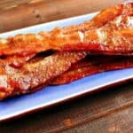 Oven baked bacon on a blue serving tray.