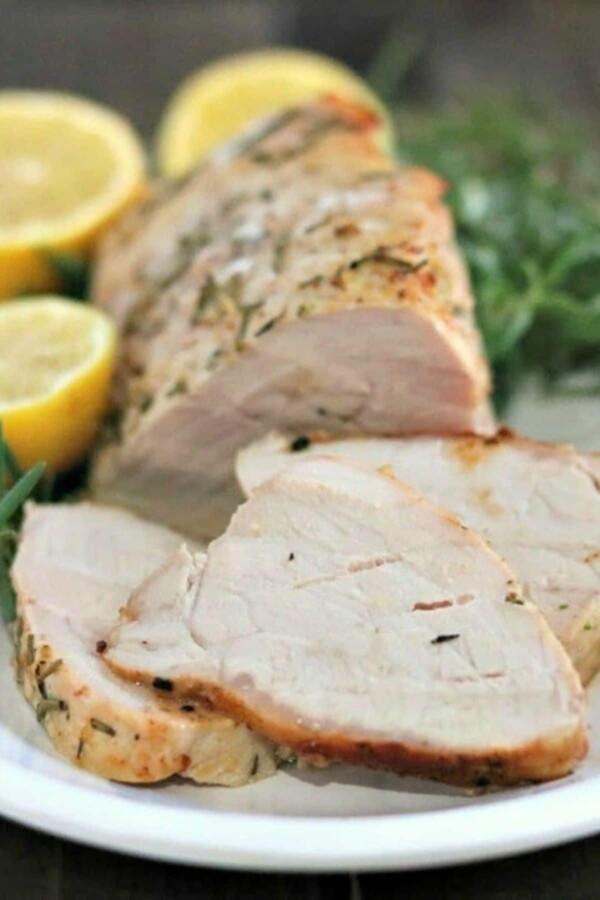 pork tenderloin slices on a white plate with lemons and rosemary