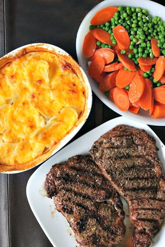 scalloped potatoes in a baking dish with steaks and carrots with peas