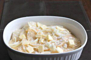 dotting butter on scalloped potatoes