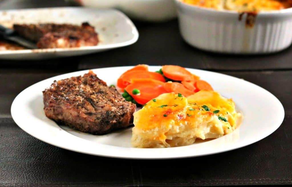 scalloped potatoes on a plate with steaks and carrots