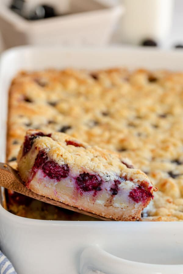 blackberry pie bars in a baking dish being removed