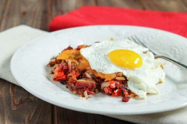 Corned beef hash with a fried egg on a white plate.