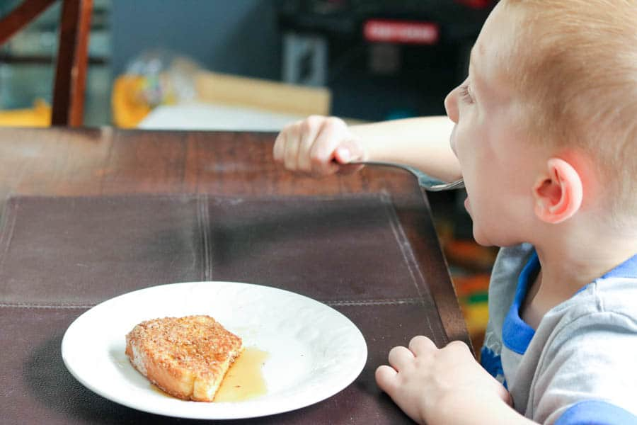 Child eating crunchy French toast at the table.