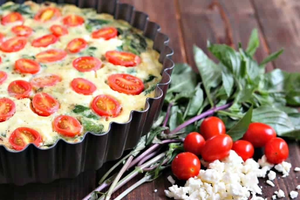 crustless quiche in the baking tin with basil, tomatoes and feta