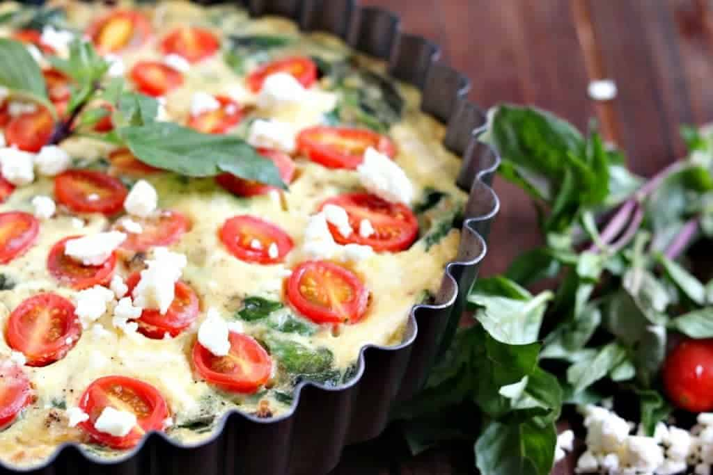Spinach is the star of the show in this healthy crustless quiche with tomatoes, onions and feta. Eaten warm, room temp, or chilled-this is a delicious dish!