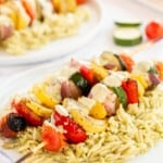vegetable skewers on a bed of orzo on a white plate