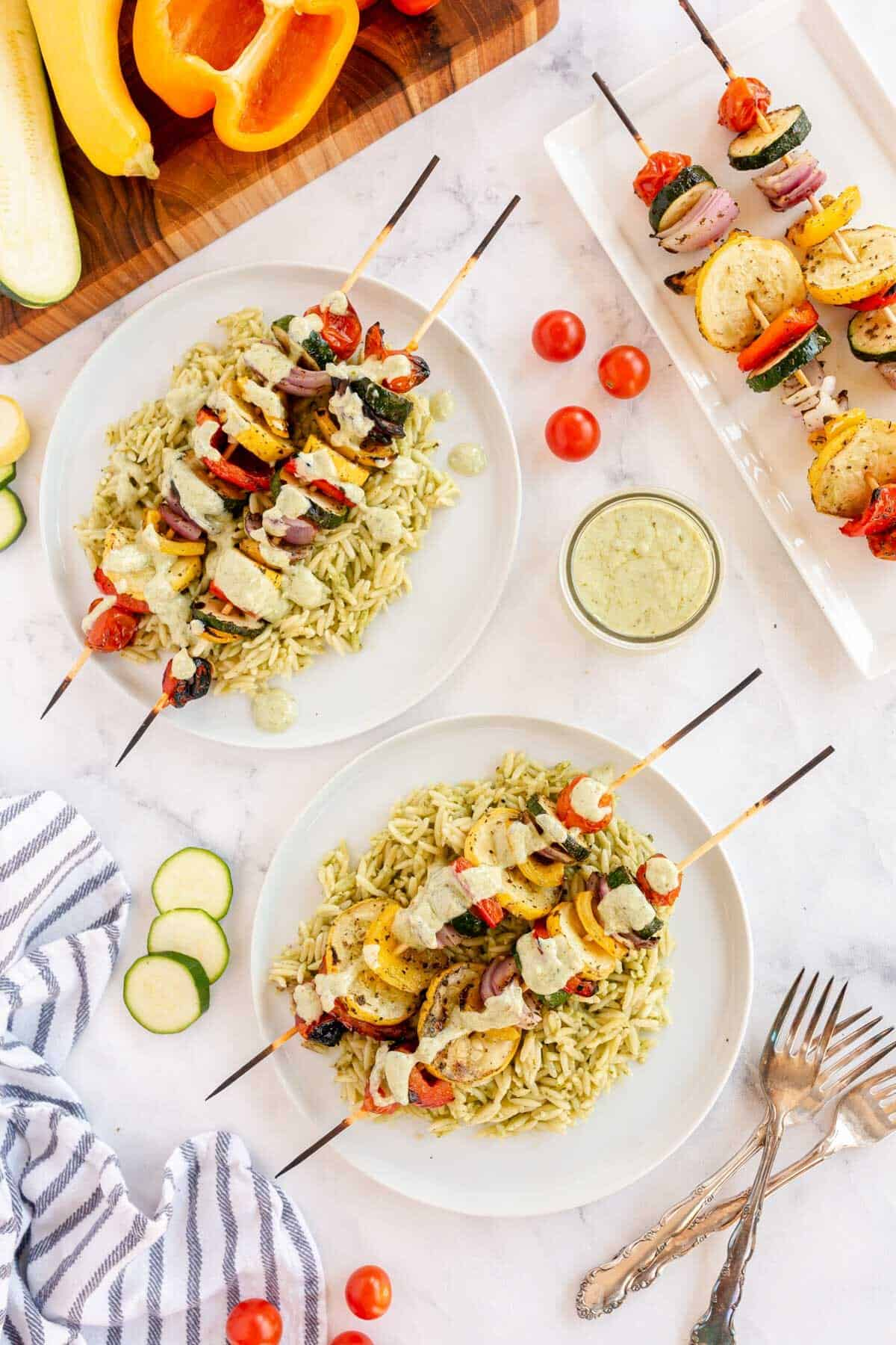 overhead shot of vegetable skewers on a bed of orzo on a white plate