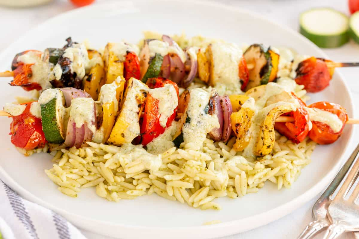 vegetable kabobs on a bed of orzo on a white plate