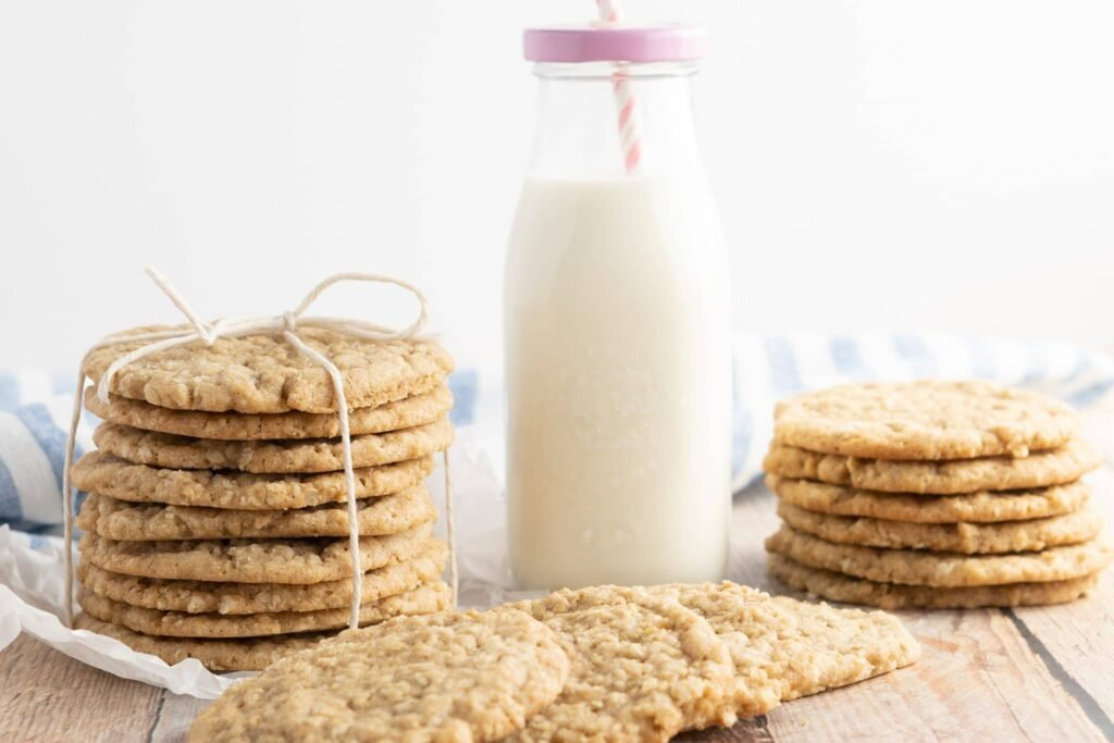 oatmeal cookies stacked and tied with twine, with a bottle of milk and pink lid