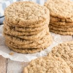 oatmeal cookies stacked on a plate with a striped napkin