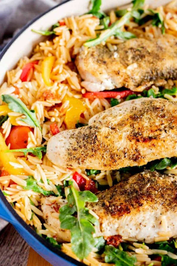 chicken and orzo in a blue skillet