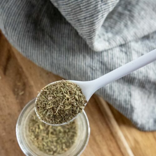 seasoning blend in a jar with a white spoon