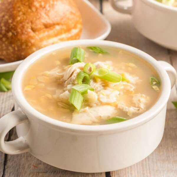 square pic of asian chicken soup in a white bowl