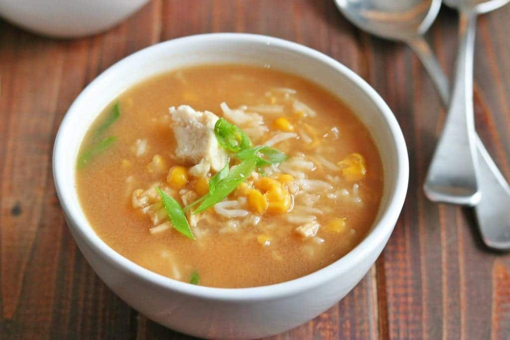 chicken corn soup with scallions in a white bowl