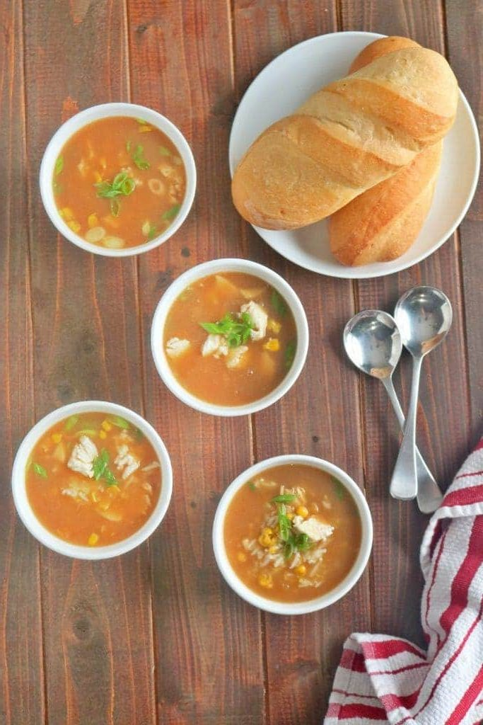 chicken corn soup in bowls with a loaf of bread