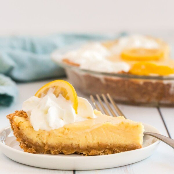 lemon pie on a white plate with a fork