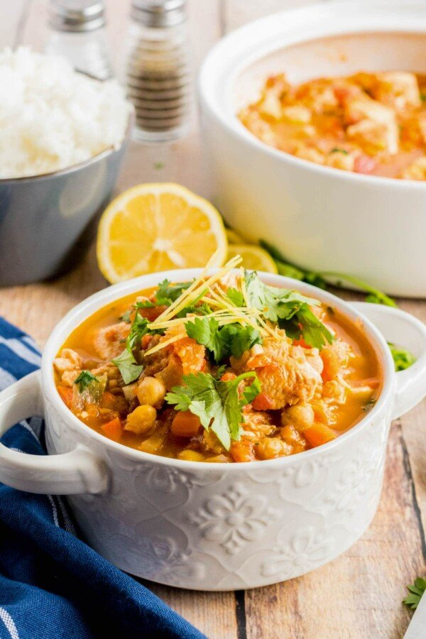 chicken stew in a white bowl with lemon and cilantro
