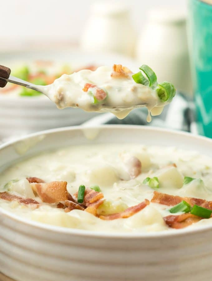 clam chowder in a white bowl with a spoon