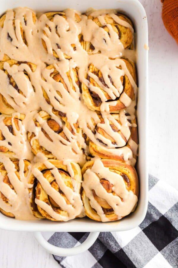 frosted pumpkin cinnamon rolls in a white casserole