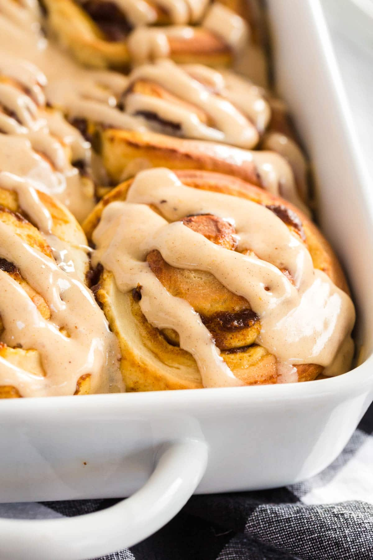 pumpkin cinnamon rolls with frosting in a white casserole