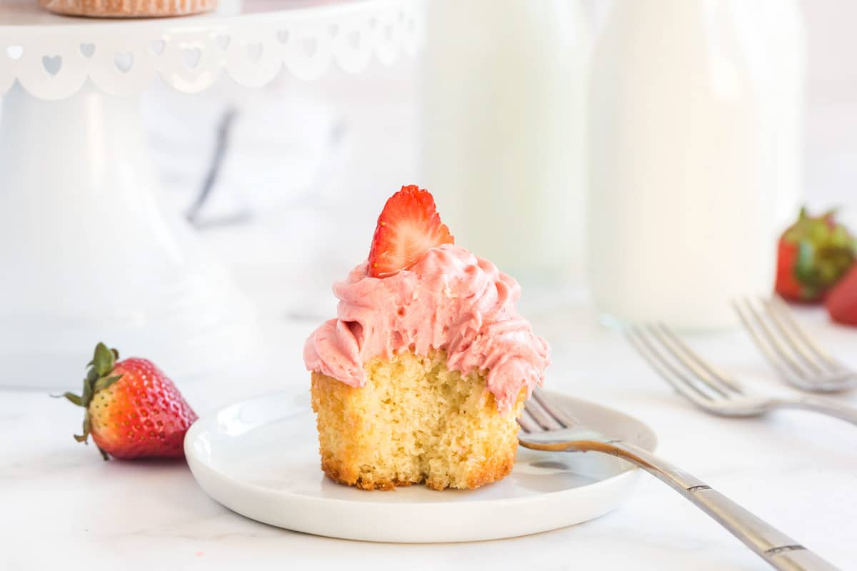 vanilla cupcake cut in half on a white plate with a strawberry