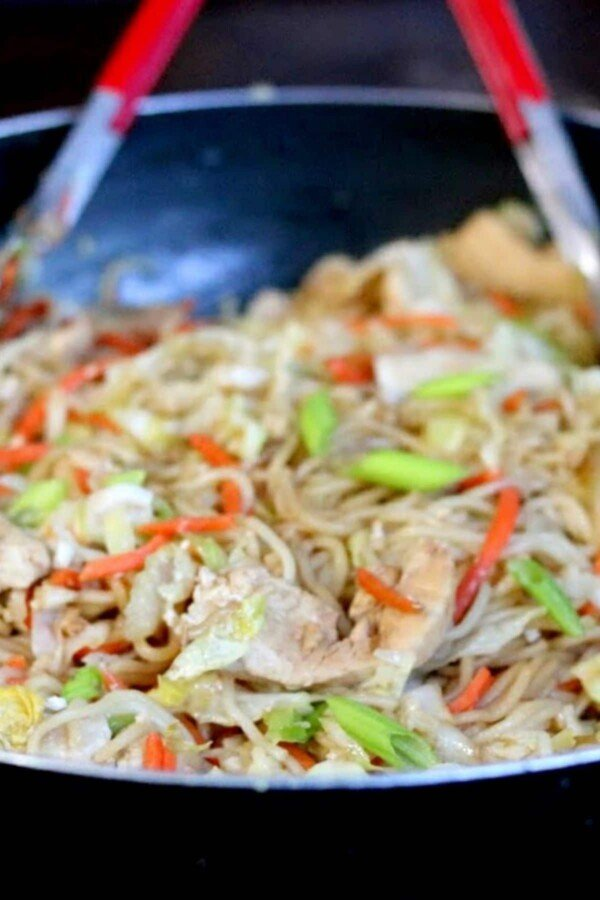 asian chicken noodles in a wok with red tongs
