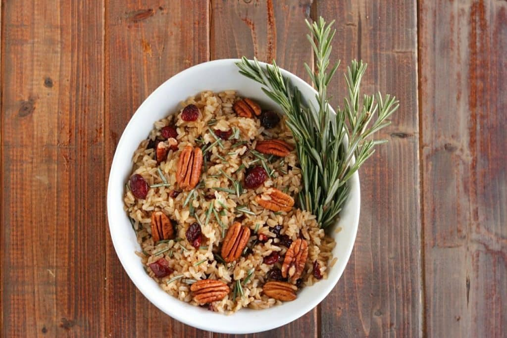 brown rice pilaf with rosemary on a wood board