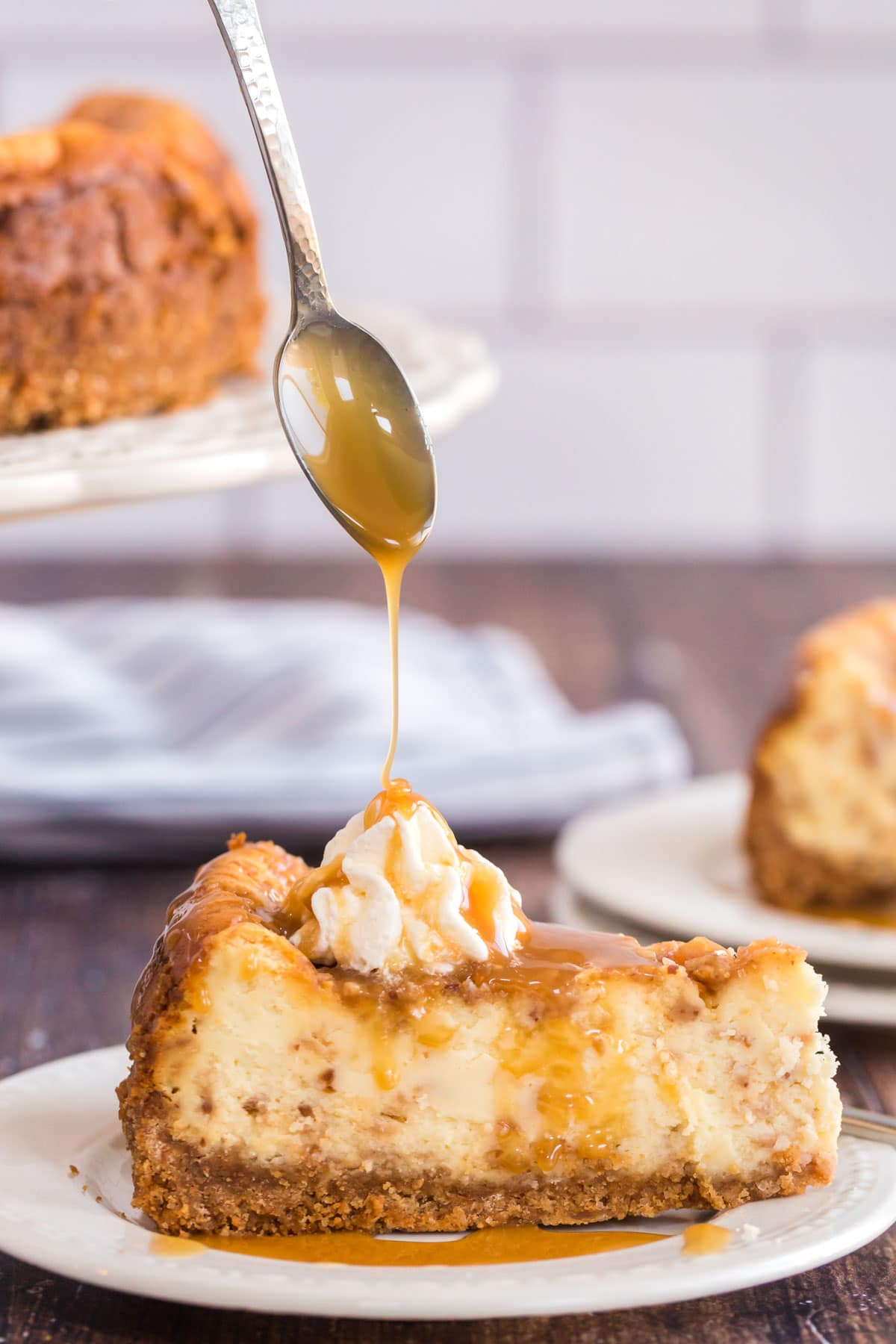 caramel sauce being drizzled over cheesecake