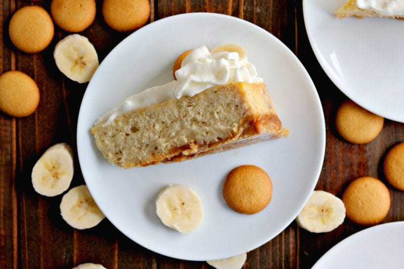 Overhead shot of banana cream cheesecake on white plate surrounded by Nilla wafers and banana slices on wood table.