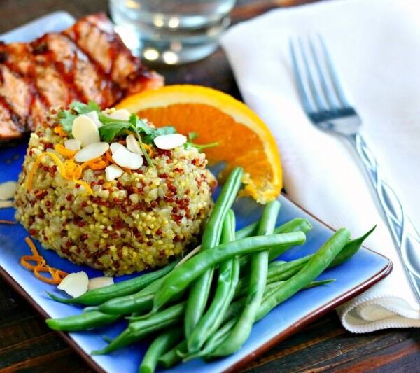 Fresh ginger orange quinoa with green beans, steak, and slice of orange on a blue plate.