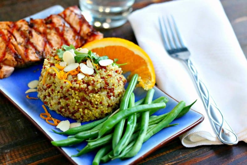 Orange scented quinoa with ribs, green beans, and orange wedge on blue plate with fork, napkin, and glass on the side on wood table.
