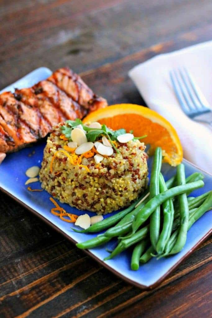 Orange scented quinoa with ribs, green beans, and orange wedge on blue plate with fork and napkin on the side on wood table.