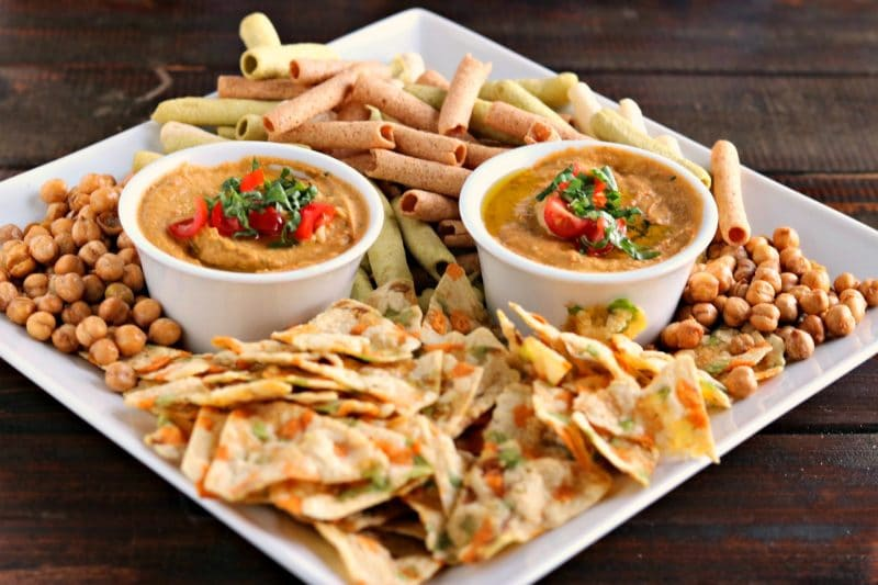 Two dipping cups of tomato basil hummus surrounded by chickpeas, chips, and veggie straws on white serving plate on wood table.