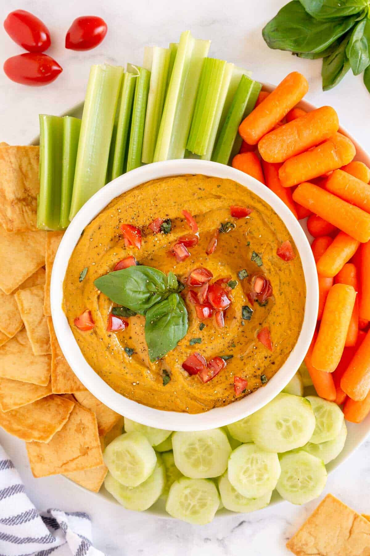 Tomato Basil Hummus in a bowl with dippers surrounding