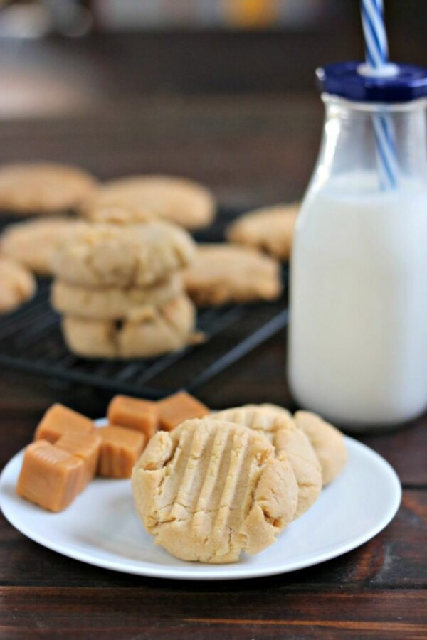 vanilla caramel cookies on a white plate with a cooling rack and milk bottle