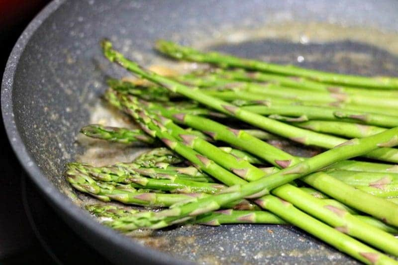 Closeup of asparagus spears in skillet ready to be cooked.